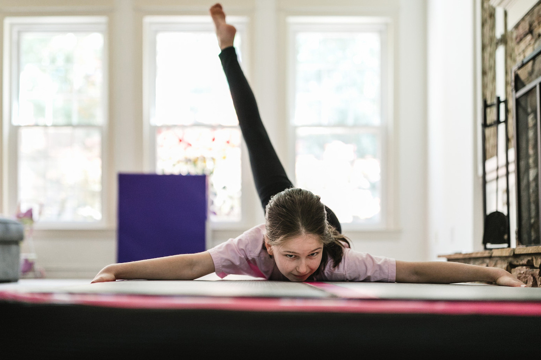 girl laying on her stomach on a gymnastics mat while kicking her leg above her head behind her
