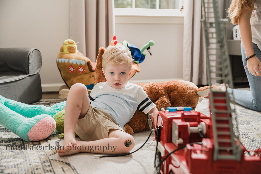 serious toddler sitting on the floor of his room among his toys