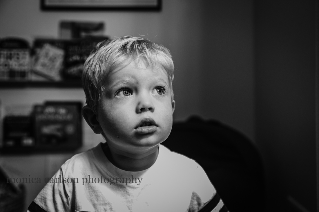 black and white portrait of a little boy looking out a window