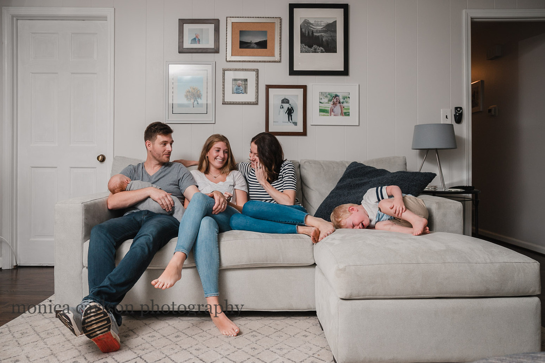 family giggles on the living room couch as a toddler throws a fit