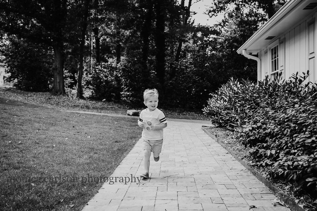 blonde boy running down a path outside his home