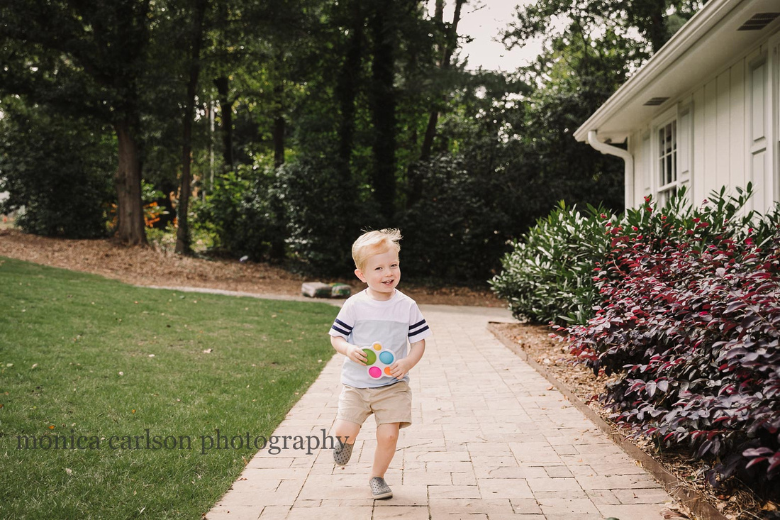 blonde boy running outside his home