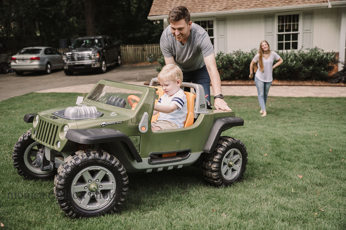father helping his toddler drive a toy truck