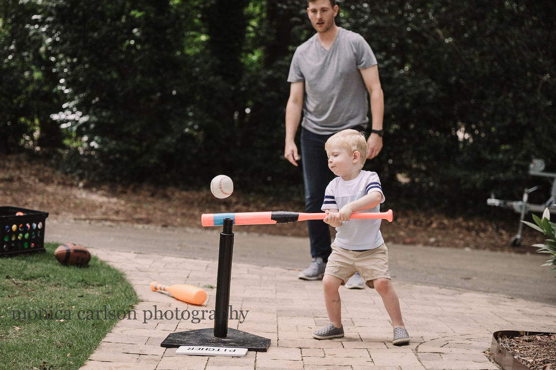 toddler playing t-ball with his father