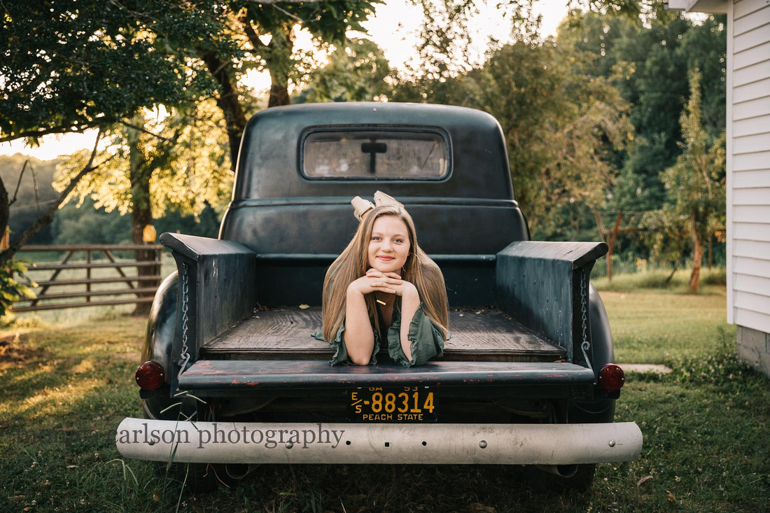 high school senior laying on the bed of a antique bus by monica carlson