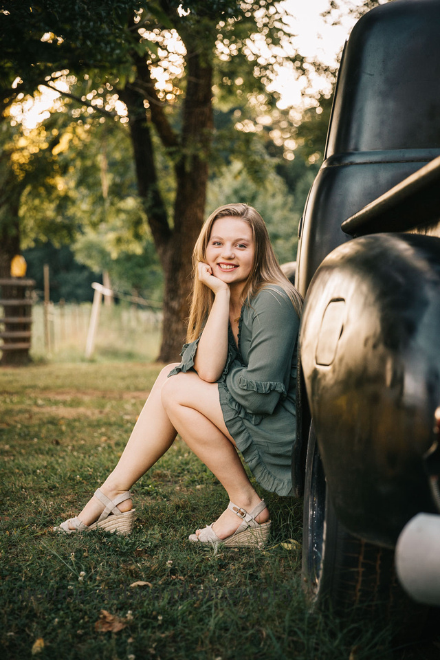 teen girl sitting in the tire wheel of a truck during a senior photo session