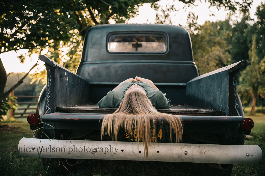 teen aged girl laying on a her back on the back of a truck
