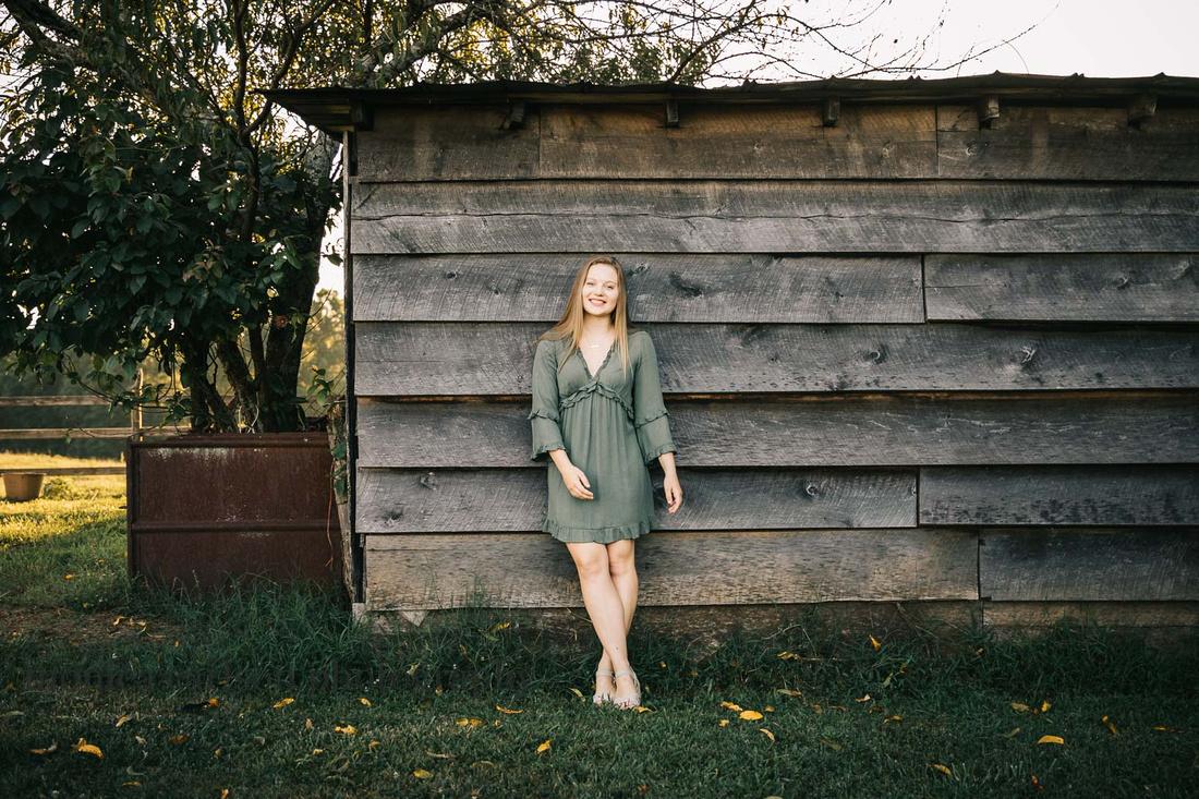 senior girl leaning against a barn during her senior session