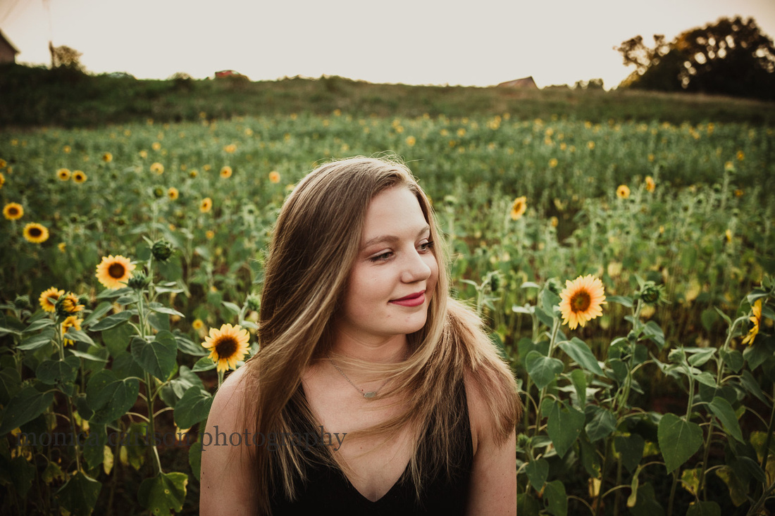 girl standing in a sunflower field with her hair blowing in the wind