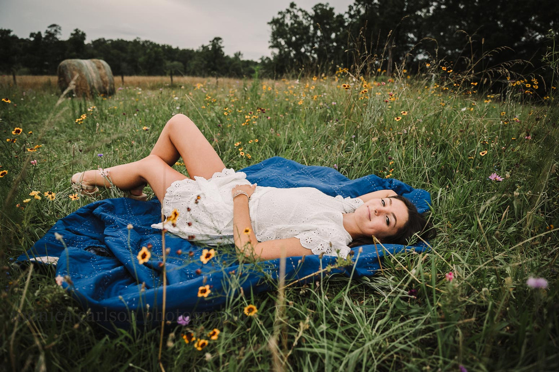 teen girl lays on a blanket in a wild flower field at Prospect farm