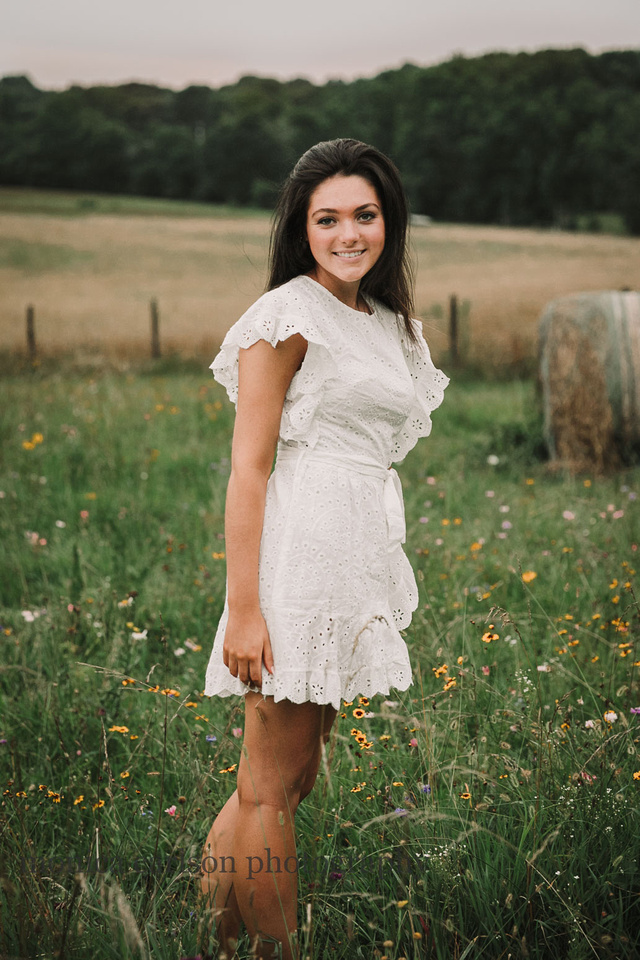 High school senior standing on a flower field on a farm