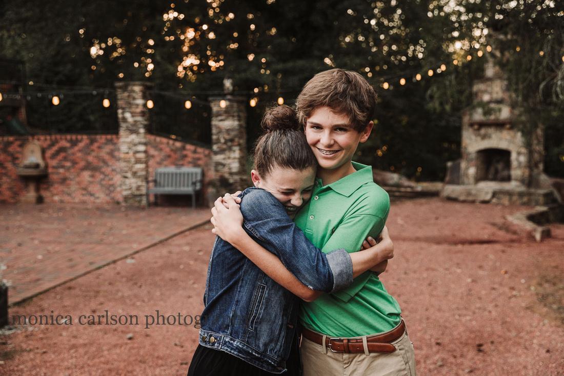 Teen girl hugs her older brother gleefully by monica carlson