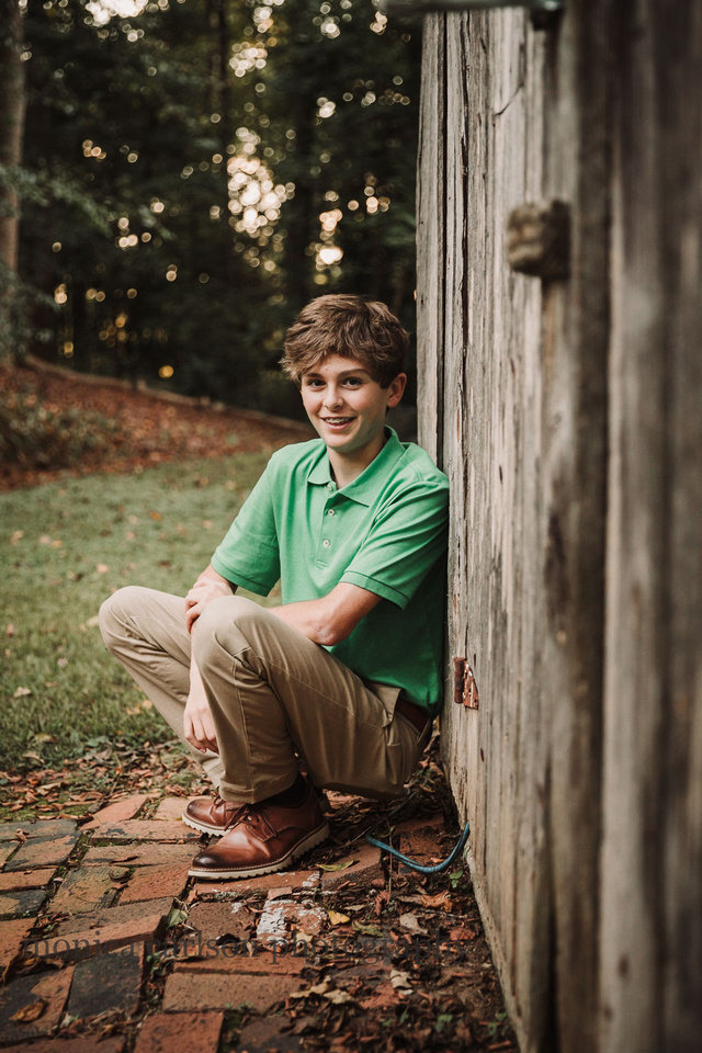 teen boy squatting in front of a wooden structure by monica carlson