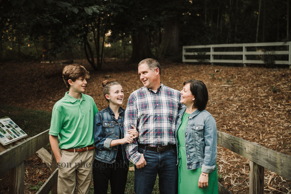 happy family chats on a wooden bridge in Roswell, GA