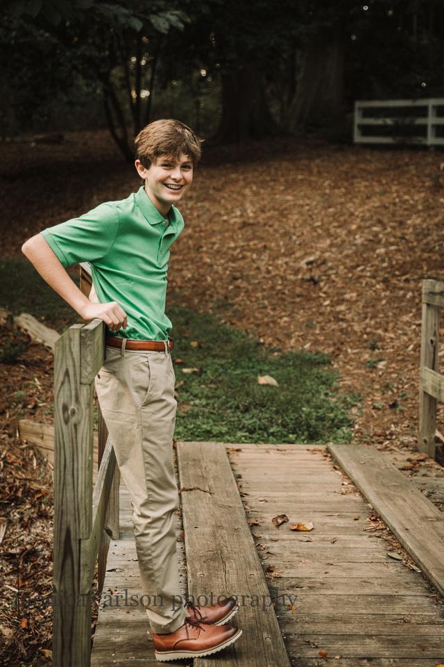 teen boy leaning against a wooden bridge