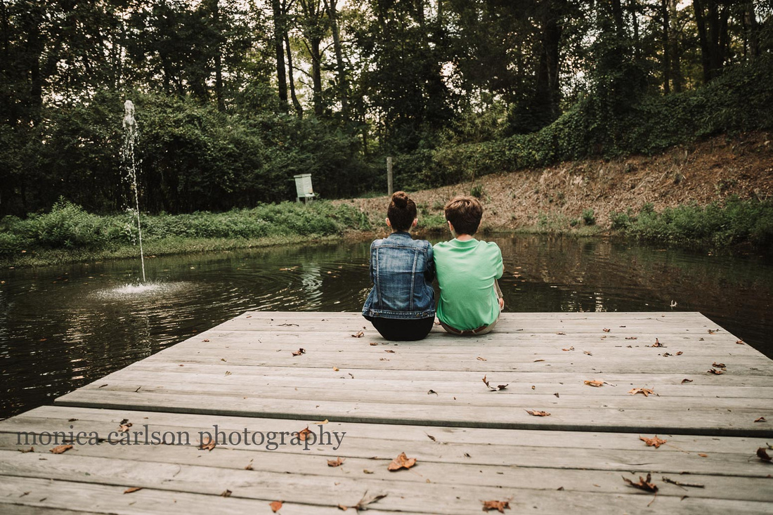 siblings bond while sitting on a dock in front of a pond