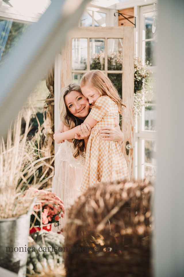 mother hugging her red haired daughter as seen through a greenhouse window