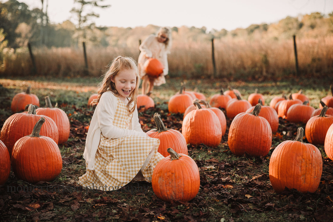 little girl happily looks at a pumpkin