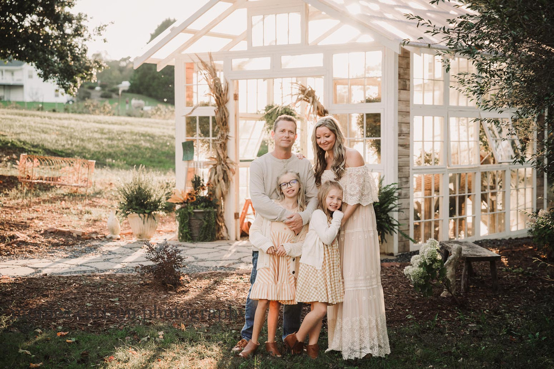 portrait of a family in front of a greenhouse by monica carlson
