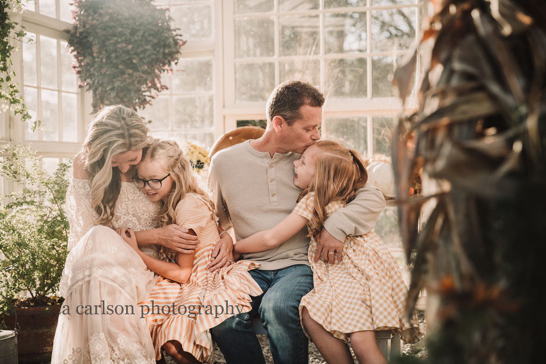 family of four hugging each other in a farm house