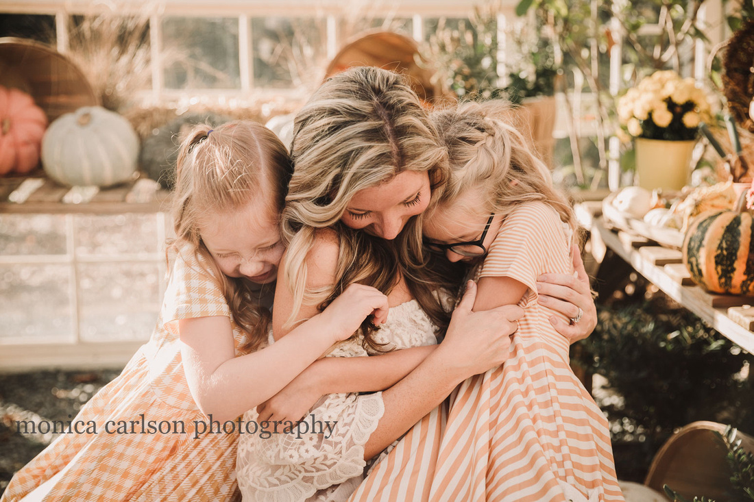 blonde and red haired girls hugging their mother during a greenhouse session