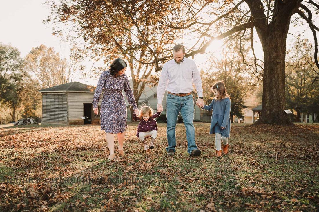 family of four walking in golden light