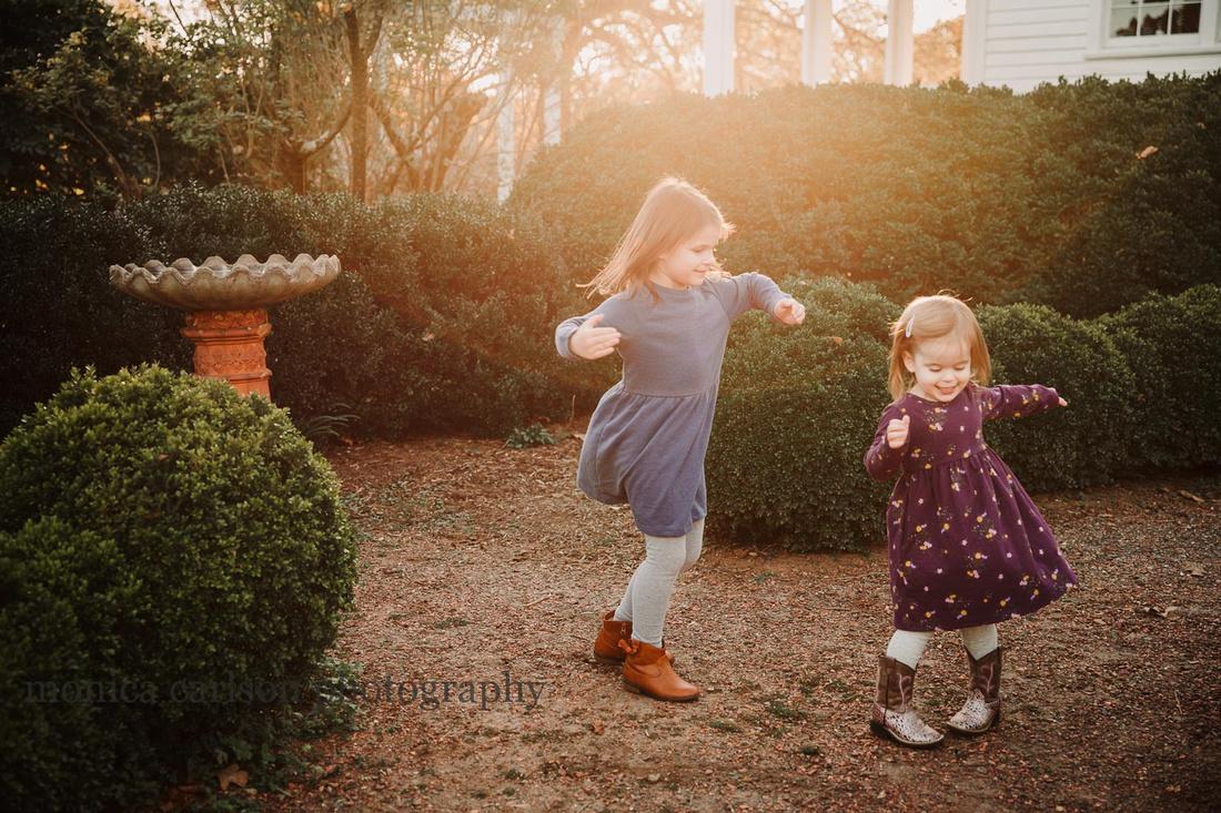 sisters spinning in golden light in Roswell, GA