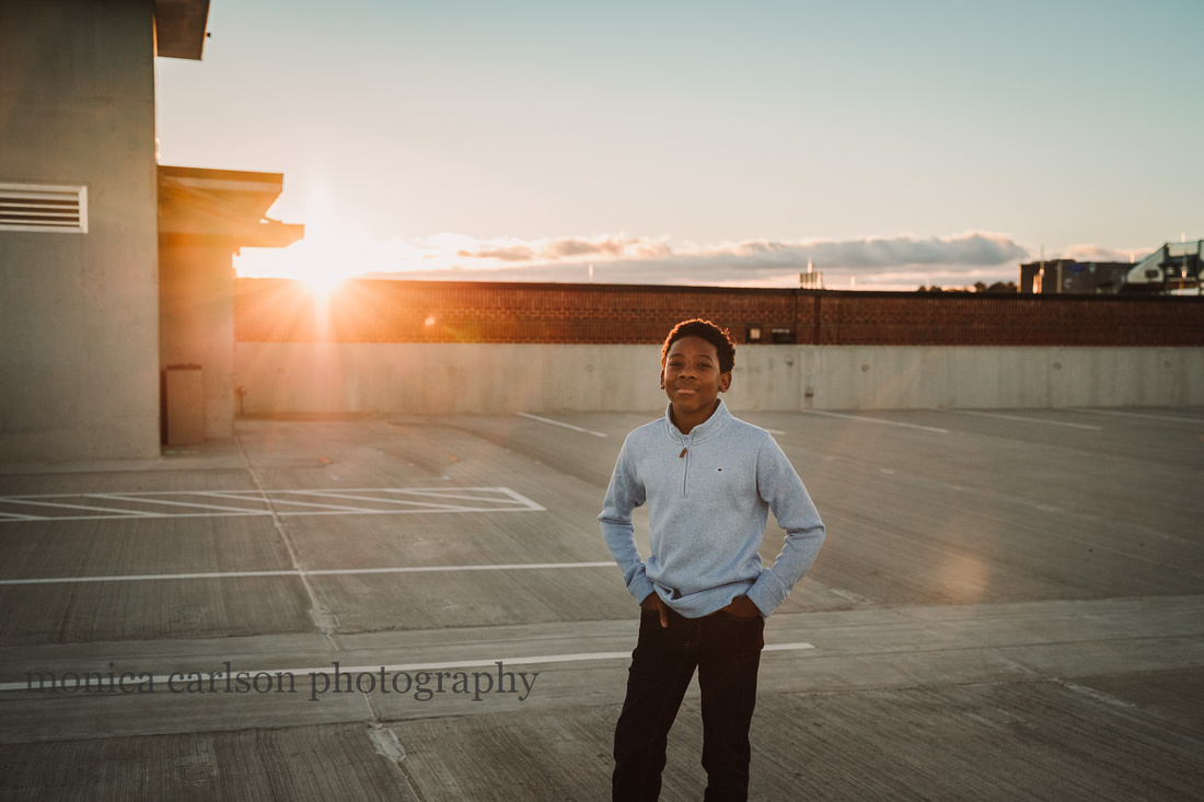portrait of a african american boy on a roof top parking lot at sunset
