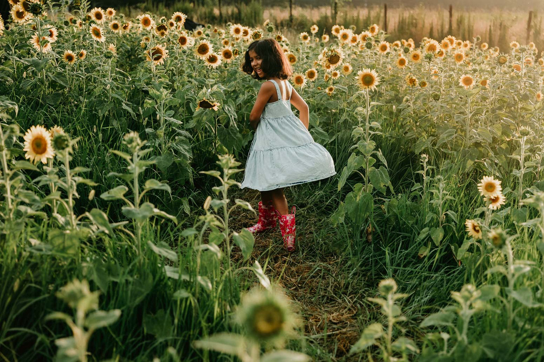 elementary aged girl spinning on a sunflower field while wearing rain boots
