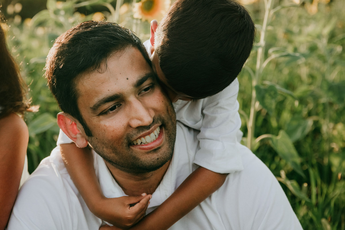 indian father get sneggles from his pre school son from behind during a family photo shoot